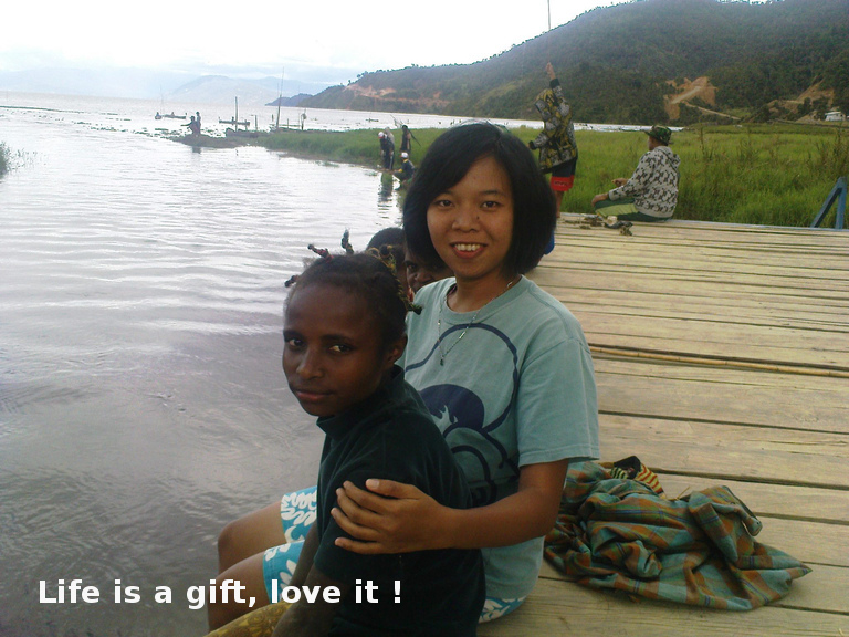 Life is a gift, love it! - Sinthya with a Papuan kid in Paniai lake, Papua