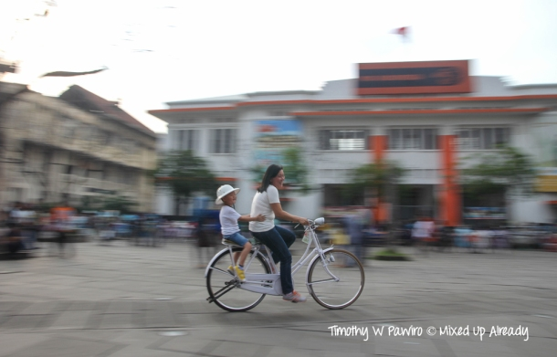 Indonesia - Jakarta - Kota Tua - Taman Fatahillah - A mother is riding a bike with her son (Panning)